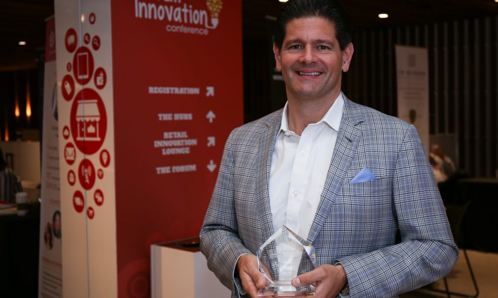 "BEDGEAR's Eugene Alletto poses with his Retail Innovator Award. He won in the ""Disruptor"" category."
